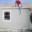 Stock Photo: Hispanic mon roof looking at ladder