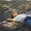 Stock Photo: AfricAmericgirl laying on picnic table