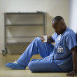 African American male doctor sitting on floor — Stock Photo