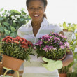 Senior African American woman holding potted plants — Foto Stock