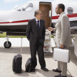 Multi-ethnic businessman talking next to airplane — Stock Photo