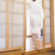 Mixed Race women walking into Shoji wall spa room — Stock Photo