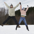 Mixed Race couple jumping in snow — Stock fotografie