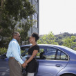 African couple smiling at each other next to car — Stock Photo