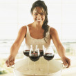 Hispanic woman carrying tray of wine glasses — Stock Photo
