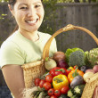 Asian woman holding basket of vegetables — Stock Photo