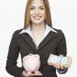 Hispanic businesswoman holding piggy bank and money — Stock Photo