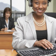 African businesswoman wearing headset — Stock Photo