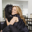 Hispanic woman hugging dog — Stock Photo