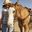 Hispanic woman standing next to horse — Stock Photo