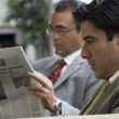 Hispanic businessman reading newspaper — Stock Photo