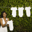 Hispanic woman hanging baby clothing clothes — Foto de Stock