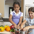 Mixed Race sisters preparing food — Stock Photo