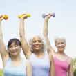 Multi-ethnic senior women lifting weights — Stock Photo