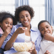 African American mother and children eating popcorn — Stock Photo
