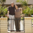 Senior Hispanic couple in front of house — ストック写真