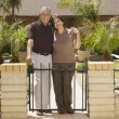 Senior Hispanic couple in front of house — Стоковая фотография