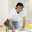 Mixed Race man writing on blueprints — Stock Photo
