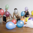 Hispanic family blowing up balloons - Stock Photo