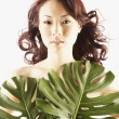 Nude Asian woman covered by large leaves — Stock Photo