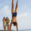 South American man doing handstand on beach — Stock Photo #23308598