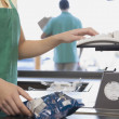 Female grocery clerk ringing up item — Stock Photo