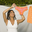 Hispanic woman hanging laundry on clothes line — Stock Photo