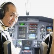 Asian male pilot in airplane cockpit — Stock Photo