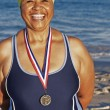 Mixed Race woman with medal on beach — Stock Photo
