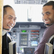 Multi-ethnic male pilots in airplane cockpit — Stock Photo