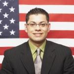empresario hispano delante de la bandera americana — Foto de Stock