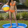Hispanic woman standing in kiddie pool — Stock Photo