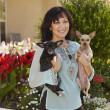 Hispanic woman holding dogs — Stock Photo