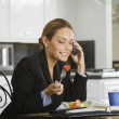 Hispanic businesswoman eating breakfast — Stock Photo