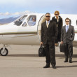 Multi-ethnic businesspeople in front of airplane — Stock Photo #23309150