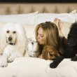 Hispanic woman laying on bed with dogs — Stock Photo #23309330