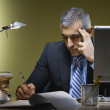 Middle Eastern businessman writing at desk — Stock Photo #23309344