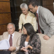 Hispanic businesspeople discussing paperwork — Stockfoto