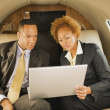 Stock Photo: AfricAmericbusinesspeople on airplane