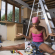 African woman shrugging shoulders at power tools — Stok fotoğraf