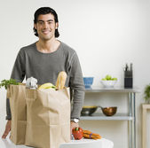 Mixed Race man next to grocery bags — Stok fotoğraf