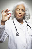 Senior Hispanic female doctor holding medication — Stock Photo