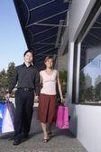 Asian couple carrying shopping bags — Stock Photo