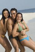 Hispanic friends hugging at beach — Stock Photo