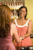 African American female sales clerk taking credit card — Stock Photo
