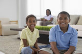 Multi-ethnic brother and sister with mother in background — Stock Photo