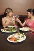 Multi-ethnic women toasting at restaurant — Stock Photo