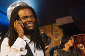 African man talking on cell phone at nightclub — Stock Photo