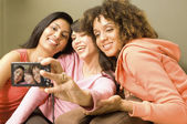 Multi-ethnic women taking own photograph — Stock Photo