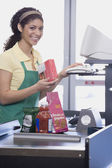 Mixed Race female grocery clerk ringing up items — Stock Photo